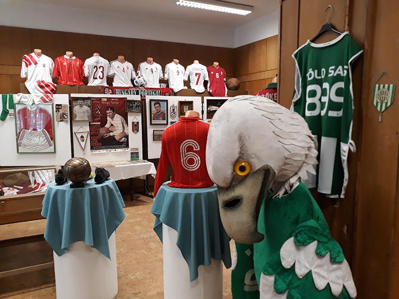 Az FTC korábbi kabalája, a zöld sas, a háttérben magyar válogatott, köztük Puskás Ferenc emléktárgyak